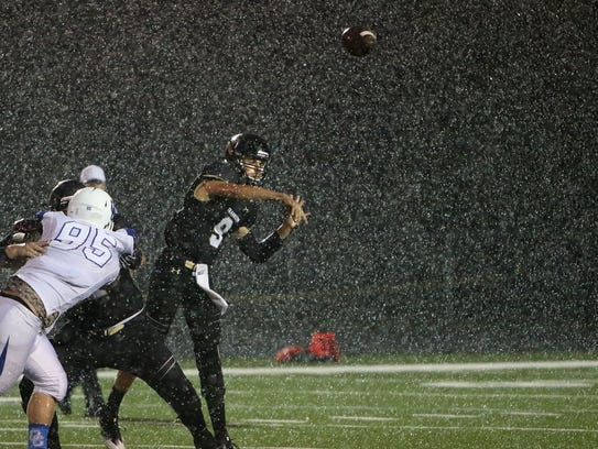 Under a heavy rain, Franklin quarterback Max Alba lets