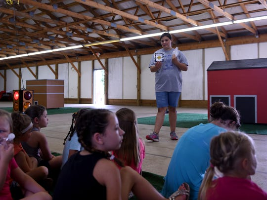Safety City volunteer Tavia Cooper, 14, quizzes kids on what different road signs mean during the Safety City camp at the Coshocton County Fairgrounds.