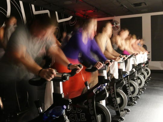 Spin cyclists are a blur of action as they spin to