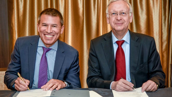 Norwegian Cruise Line president and CEO Andy Stuart and Meyer Werft managing partner Bernard Meyer sign documents marking the delivery of the 3,883-passenger Norwegian Joy on April 27, 2017.