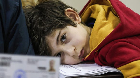 Ward Faraj al-Jamous, a Syrian refugee, rests his head on a stack of documents, after his family was prevented from travel to the U.S. after Trump blocked entry to citizens from seven Muslim-majority countries.