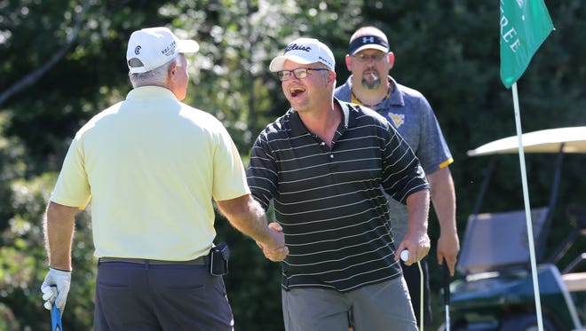 Al Hubert shakes the hand of Russ Maffett after they had completed 18 holes at the Oaktree Golf Club.