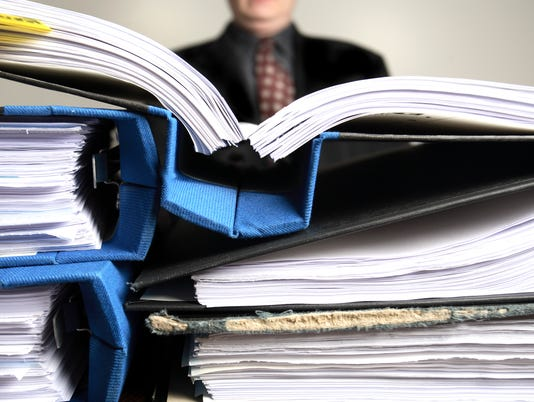 Businessman saturated with paperwork