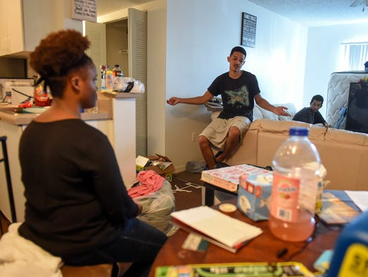Sabal Chase resident Tony Cureton, 21, (center) discusses