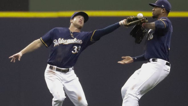 Brewers outfielders Domingo Santana (right) and Brett Phillips nearly collide as Phillips can't catch a ball hit by the Giants' Eduardo Nunez during the ninth inning Monday.