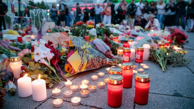 People mourn near the crime scene at OEZ shopping center in Munich the day after a shooting spree left nine victims dead.