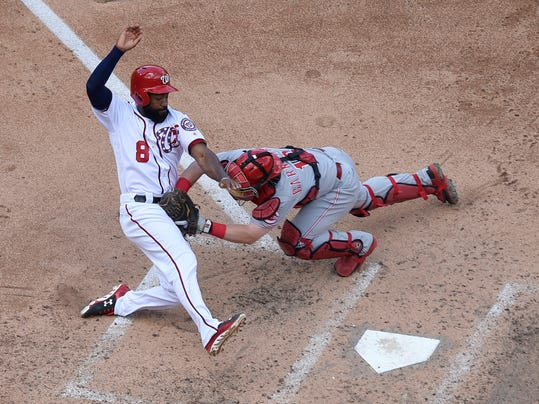 Washington Nationals' Brian Goodwin (8) is tagged out at home by Cincinnati Reds catcher Tucker Barnhart, right, during the fifth inning of a baseball game, Sunday, June 25, 2017, in Washington. (AP Photo/Nick Wass)