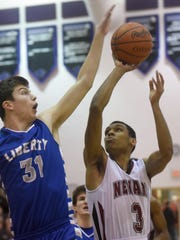 Olentangy Liberty's Brett Buzash tries to block a shot from Newark senior Justin Carter. The Wildcats defeated the Patriots 78-60 in a Division I district semifinal on Wednesday, March 8, 2017 at Pickerington North High School.