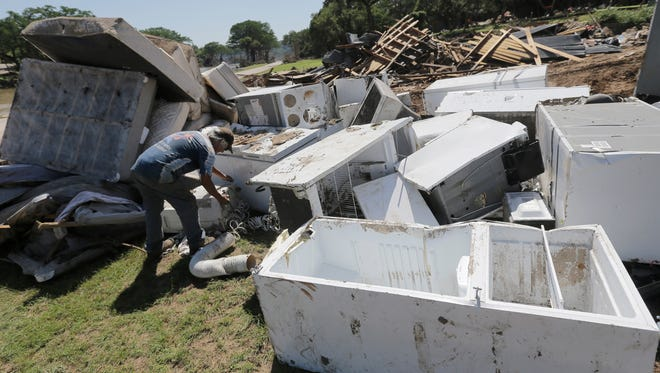 In this May 29, 2015 file photo, Johnny  Rodriguez works to salvage appliances destroyed by flooding along the Blanco River, in Wimberley, Texas. Parts of Texas were finally beginning to rebuild on Sunday from weeks of rain and flooding that have made the state a place of extremes: severe drought conditions earlier in the year that have given way to unprecedented rainfall in some areas.