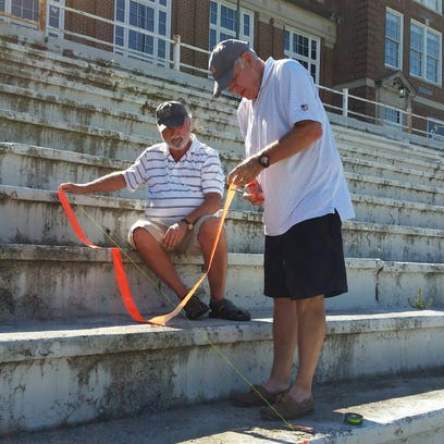 Dennis Latta and Herb Foster carefully measure out
