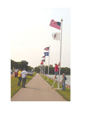 John Schueller and Jerome Bertrand, of the Servicemen's Club, raised the flags along the lake trail Tuesday morning. Watching are Public Works Director Mike Hardin and EDA Coordinator Kurk Kramer.