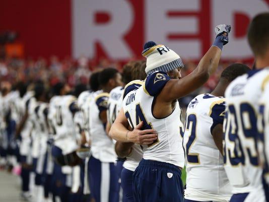 Robert Quinn raises his arm during the national anthem