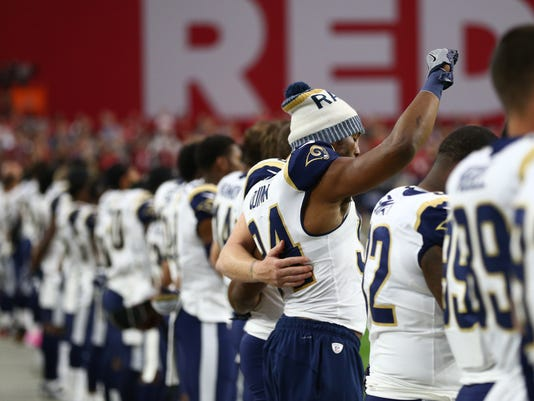 Robert Quinn raises his arm during the national anthem
