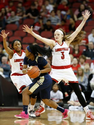 Louisville's Taja Cole, left and Sam Fuehring trapped a Pitt player in the backcourt during first half action. Feb. 28, 2016.