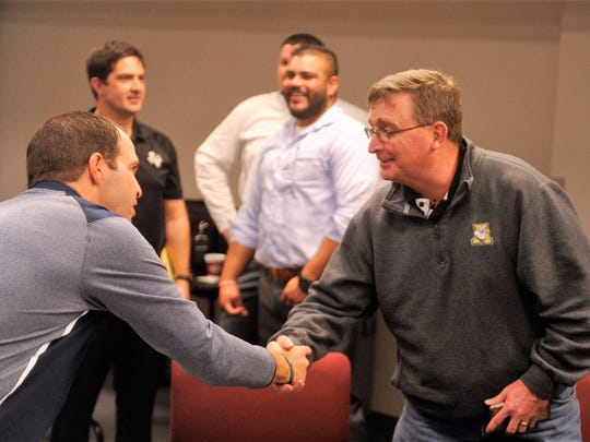 Abilene High head football coach Del Van Cox, right, shakes hands with a coach from Hurst Bell during the UIL Realignment meeting on Thursday, Feb. 1 at the Birdville ISD Fine Arts and Athletics Complex.