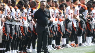 Cincinnati Bengals head coach Marvin Lewis, center, looks down the sideline as the Cincinnati Bengals lock arms during the national anthem before the Week 3 NFL football game between the Cincinnati Bengals and the Green Bay Packers, Sunday, Sept. 24, 2017, at Lambeau Field in Green Bay, Wisconsin.