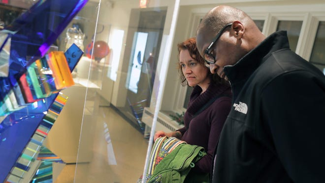 Marie Luna and Tony DeVine take time to look at a glass sculpture during the Art After Dark - Winter Solstice Edition at the Bergstrom Mahler Museum of Glass on Dec. 21 in Neenah.