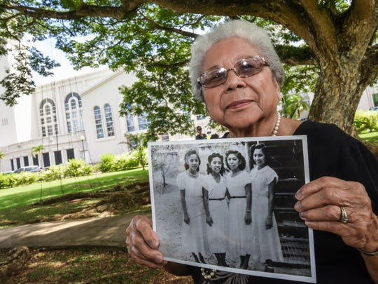 Cleotilde Bamba, 84, displays a vintage photo of her, pictured on the left, take of and her sisters during her Sweet 16 birthday, during a photo shoot at the Plaza de Espana on Wednesday, Dec. 7, 2016. Bamba also recalled memories of her First Holy Communion ceremony at the Hagåtña church, back in December 1941,  being interrupted by invading Japanese aircrafts when she was only nine-years-old.