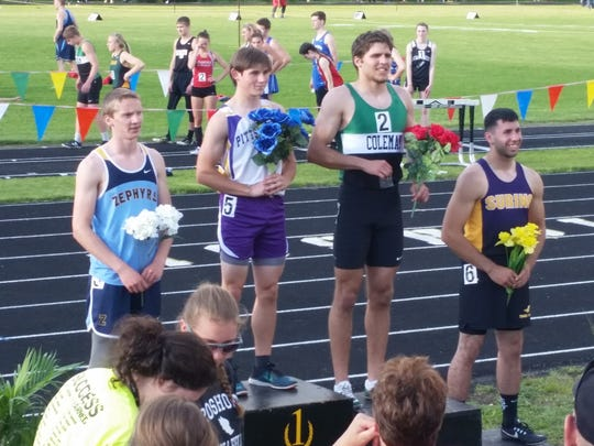 Snook (second from left) stands atop the podium after winning the 100 at the Rosholt sectional.