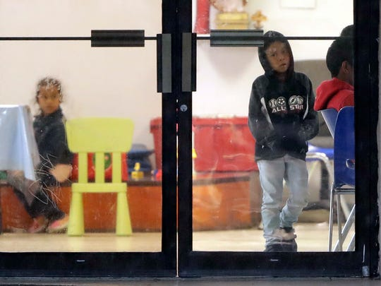 Niños inmigrantes observan a través de una puerta de vidrio en un albergue de McAllen, Texas.