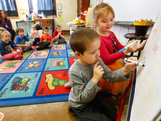 Parker Huffman, 5, left, and Chloe Reid, 4, students in Sarah Fox's Wonder Years preschool class at Bowerman Elementary School, sign their names to a letter on Wednesday, Feb. 7, 2018.
