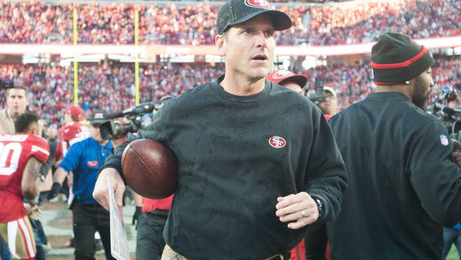 49ers head coach Jim Harbaugh leaves the field after his team defeated Arizona on Sunday.