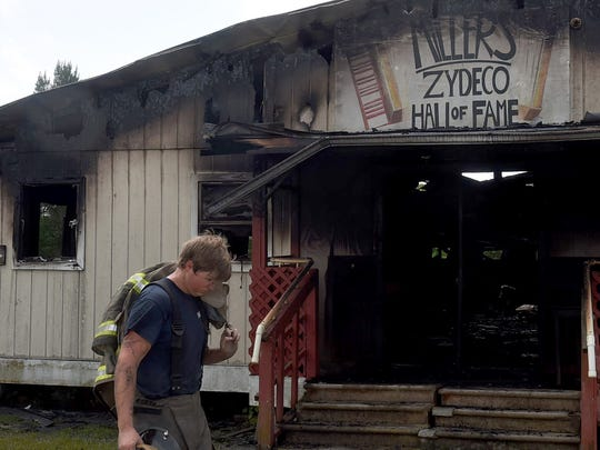 A firefighter passes in front of Miller's Zydeco Hall of Fame after battling an early morning fire there Wednesday.