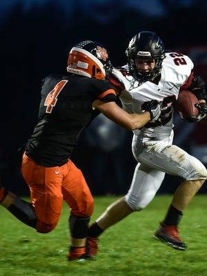 Pleasant senior running back Clay Cheney throws a stiff arm at North Union defender Tim Davis during a game earlier this year. The Spartans will play at Eastwood on Saturday at 7 p.m. in a Division V playoff game.