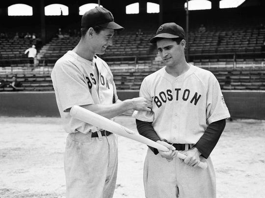 In this May 14, 1942, file photo, Boston Red Sox left fielder Ted Williams, left, tests the arm of Red Sox second baseman Bobby Doerr before their game against the White Sox, in Chicago.