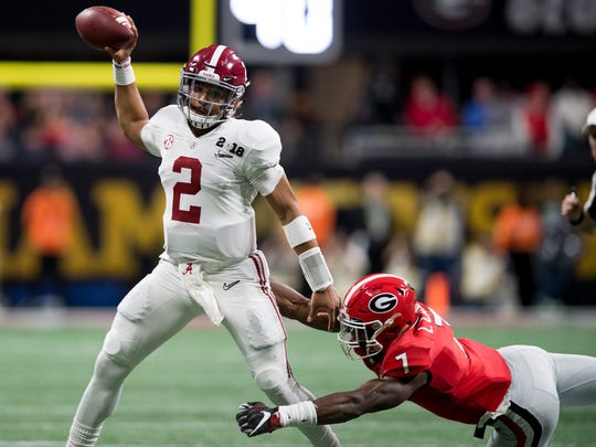 Alabama quarterback Jalen Hurts (2) throws while being