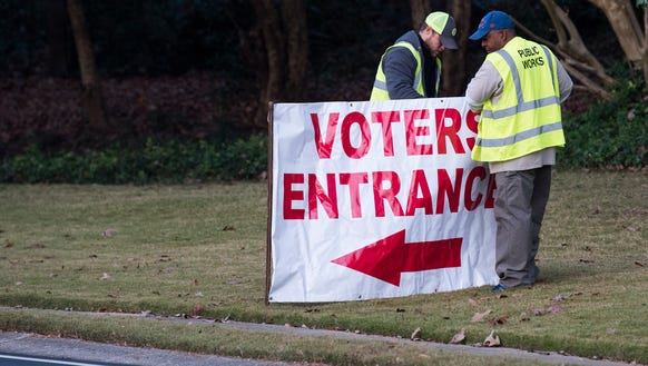 Workers put up signs directing voters in Mountain Brook,