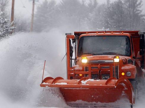 Highway crews work to clear snow from roads on Jan. 2, 2014, in Henniker, N.H.