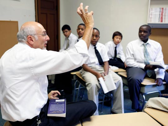 Jay Costanza raises a question about the book, Blood on the River, to seventh graders during a literacy skills class at University Preparatory Charter School for Young Men in 2010.