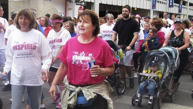 Pink-clad walkers flood Baldwin Street in downtown Elmira during the 2013 Twin Tiers Komen Race for the Cure to fight breast cancer.