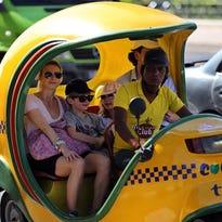 """En la imagen, turistas viajan en un """"cocotaxi"""" este en La Habana (Cuba)."""