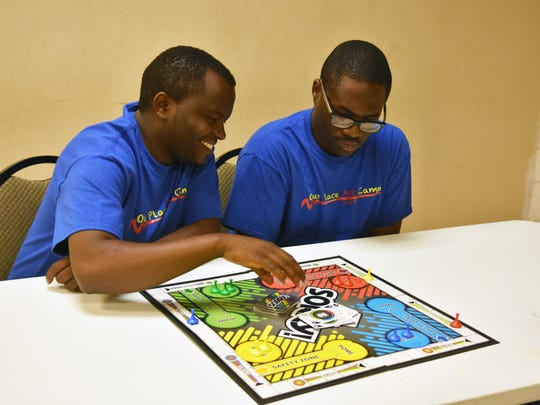 Martin Gathimbi and Derrick Freeman play a friendly game of Sorry at the Our Place Art Camp.
