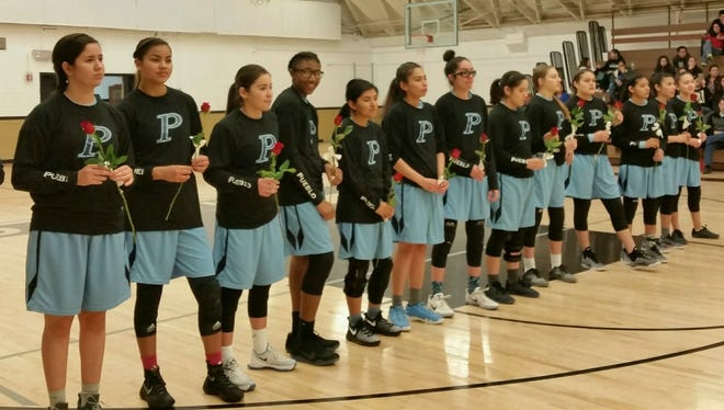 Puelbo girls basketball players each present a rose to the Douglas players before Friday's game, two days after the death of Douglas boys soccer coach Ken Cormier.