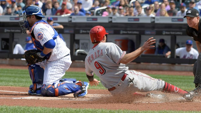 The Cincinnati Reds' Jose Peraza (9) scores on a single by Zack Cozart as New York Mets catcher Travis d'Arnaud, left, takes the throw during the first inning ofthe game Sunday, Sept. 10, 2017, in New York.