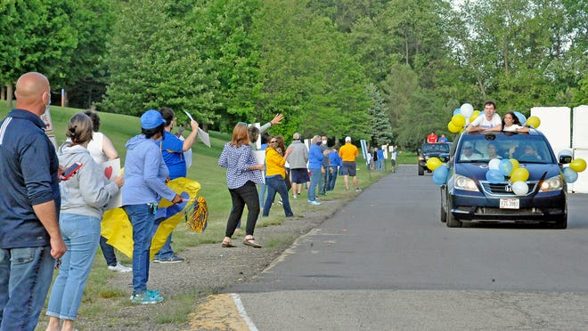 A large and loud crowd cheers Monday for members of the Wooster High School Class of 2020 during a car parade in the WHS parking lot.