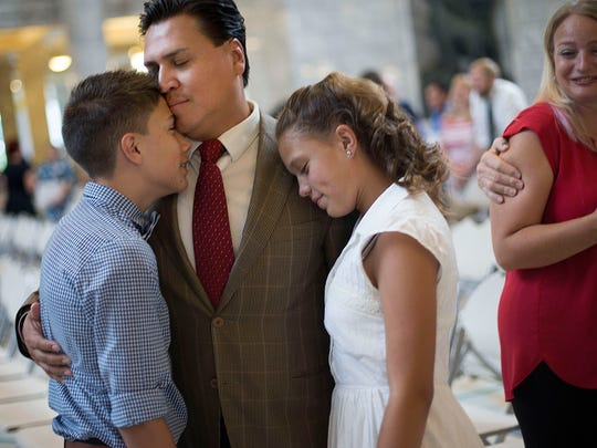 Victor Avalos, of Mexico, hugs his children, Nathan and Isabelle, as his wife, Kelly, looks on after Avalos became a citizen during a naturalization ceremony at the state Capitol in Salt Lake City on Wednesday, July 19, 2017.