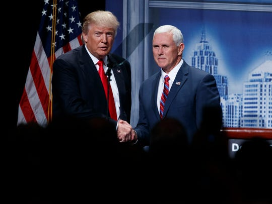 Donald Trump shakes hands with his running mate, Indiana