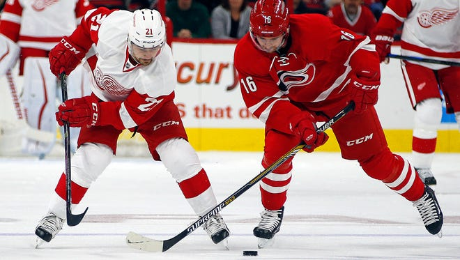 Detroit Red Wings forward Tomas Tatar, left, battles with the Carolina Hurricanes' Elias Lindholm on Oct. 10, 2015, in Raleigh, N.C.