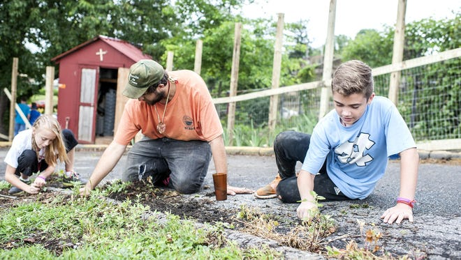 From right, Dylan Hughes, 11, Allen Doyle, 19, and Tristin Ramsey, 12, pull weeds from the side of the pavement at Haywood Street Congregation. The youths are part of Carolina Cross Connection, a nonprofit ministry that brings people from all over to do urban outreach in Asheville.