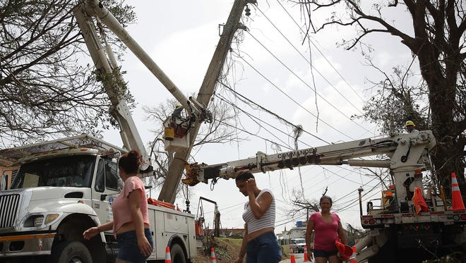 An electrical crew attempts to repair power lines that were knocked over when Hurricane Maria tore through on September 27, 2017, in Corozal, Puerto Rico.