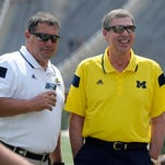 """Michigan athletic director David Brandon, right, with coach Brady Hoke, said """"new pricing is the result of positive dialogue between our students and the athletic department."""""""