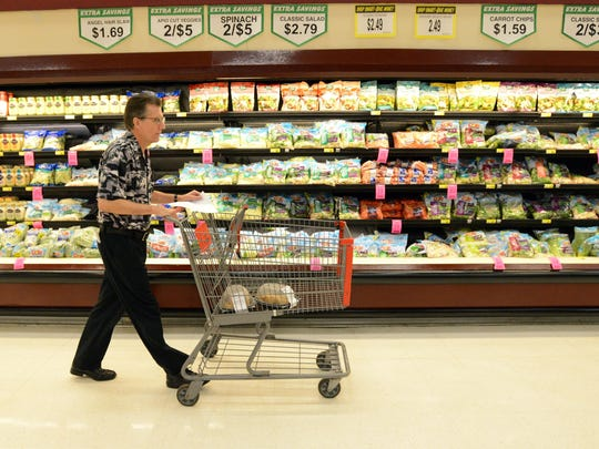Eagle-Gazette reporter Jeff Barron walks through the produce section of Carnival Foods in Lancaster.