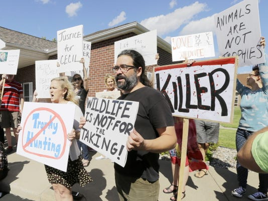 Protestors gather outside Dr. Walter James Palmer's dental office Wednesday in Bloomington, Minn. Palmer reportedly paid 50,000 to track and kill Cecil, a black-maned lion, just outside Hwange National Park in Zimbabwe.