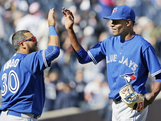Toronto Blue Jays designated hitter Dioner Navarro, left, congratulates Blue Jays relief pitcher Miguel Castro after the Jays defeated the New York Yankees 6-1 in an opening day baseball game in New York, Monday, April 6, 2015. (AP Photo/Kathy Willens)
