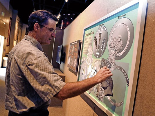 Museum director Bart Wilsey demonstrates the 'create a coin' station in the 'Mint Condition' exhibition at the Farmington Museum at Gateway Park.