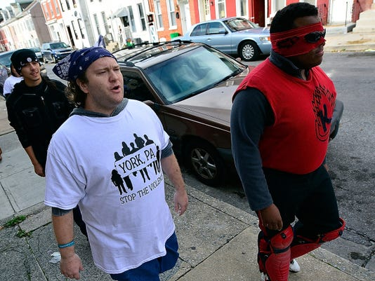 """John Beck, left, and Emil """"The Komet"""" Tucker-Orr of York City lead a march from Continental Square to Walnut Street in York during an anti-violence rally Sunday. After arriving on Walnut, the group spent several hours cleaning up litter in the neighborhood."""